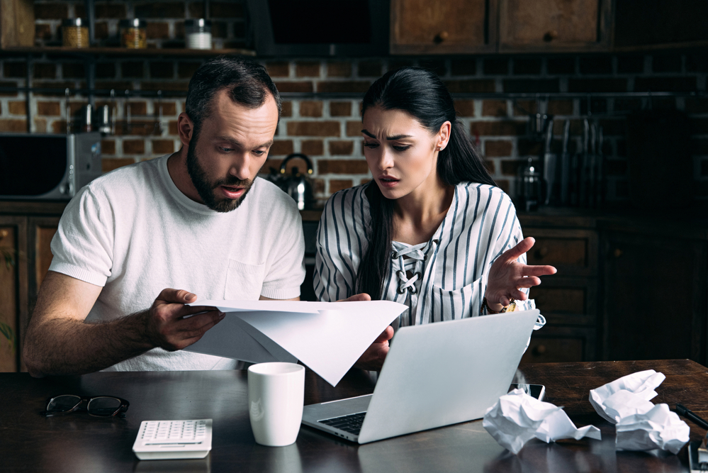 Shocked couple looking at paperwork in front of computer