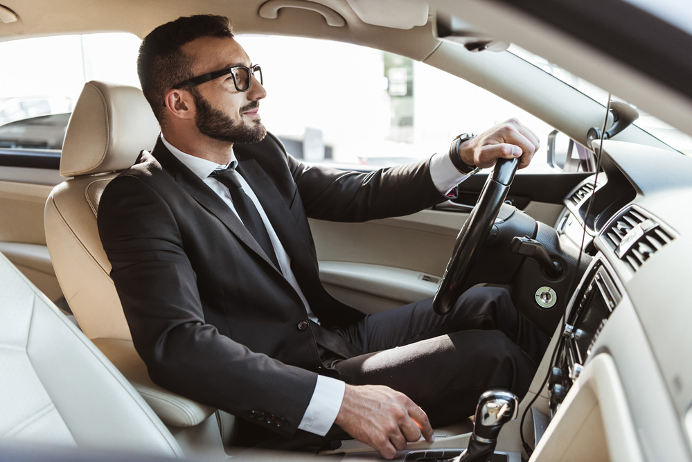 Businessman in suit driving car