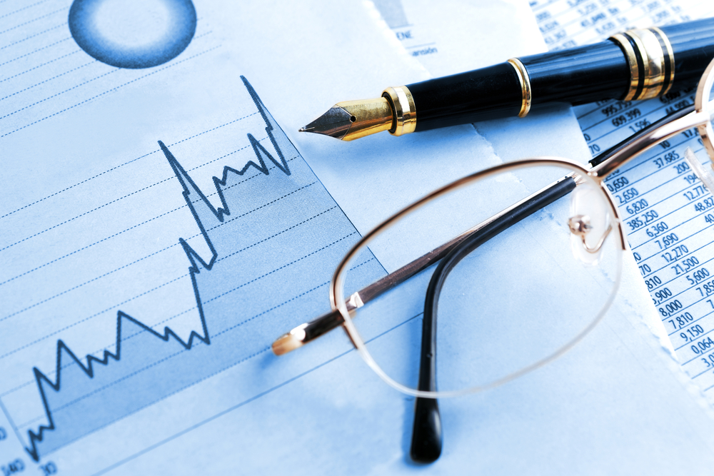 Business financials and graph with pen and glasses